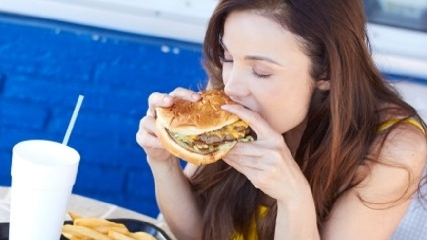 Beautiful young lady eating a tasty burger at an outdoor cafe. Horizontal Shot.