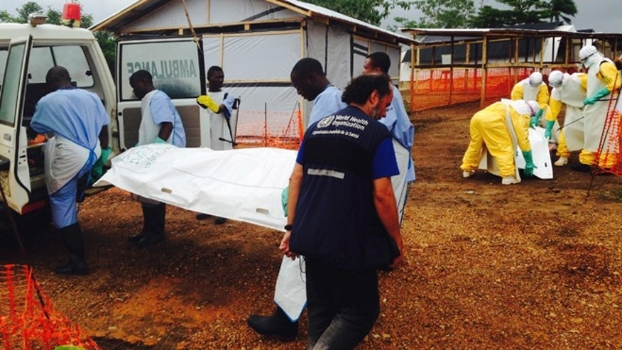 Volunteers carry bodies in a centre run by Medecins Sans Frontieres for Ebola patients in Kailahun August 2, 2014. REUTERS/WHO/Tarik Jasarevic/Handout via Reuters