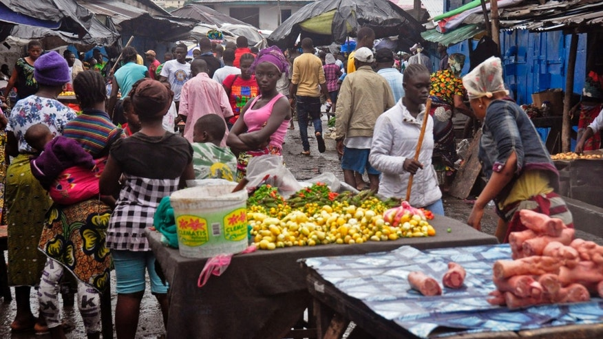 People buy foods at a local market after Liberian authorities reopened the West Point slum where tens of thousands of people were barricaded amid the countrys Ebola outbreak in Monrovia, Liberia, Saturday, Aug. 30, 2014. (AP Photo/Abbas Dulleh)