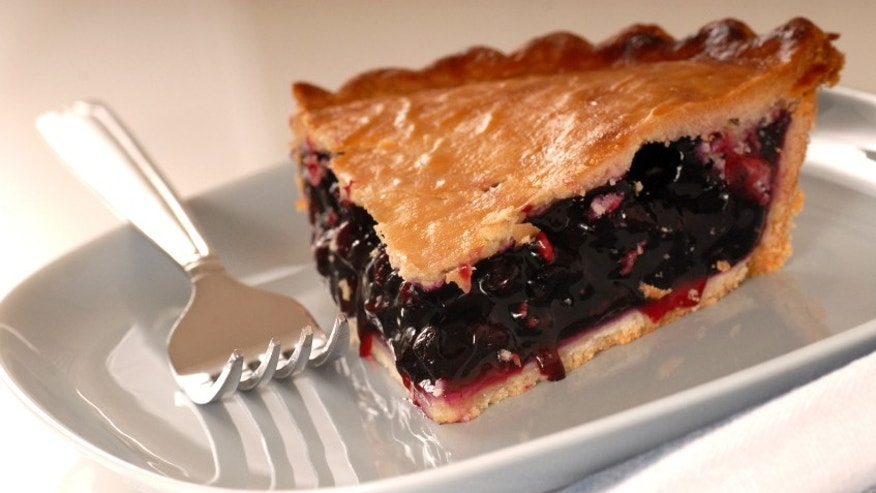 Slice of freshly baked blueberry pie with a fork