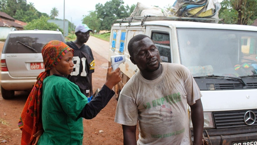 In this photo taken on Sunday, Sept. 7, 2014, a health worker, left, uses a thermometer to screen a man at a makeshift road block run by Guinean security forces outside the town of Forecariah, Guinea. (AP Photo/Youssouf Bah)