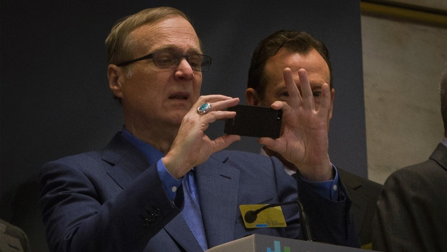 Seattle Seahawks owner and Microsoft co-founder Paul Allen takes a photo prior to ringing the opening bell at the New York Stock Exchange January 30, 2014. REUTERS/Brendan McDermid