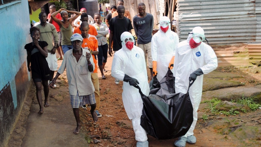 Health workers remove the body of Prince Nyentee, a 29-year-old man whom local residents said died of Ebola virus in Monrovia September 11, 2014. REUTERS/James Giahyue