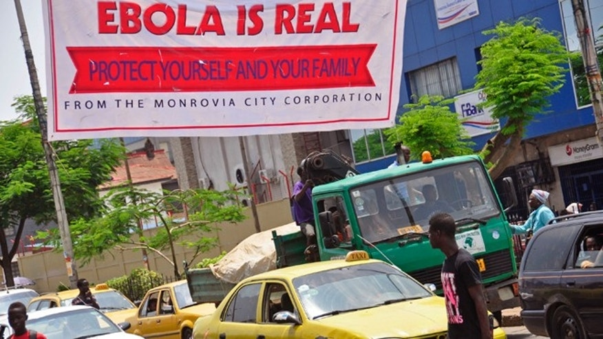 A banner reading: Ebola is real, Protect yourself and your family, warns people of the Ebola virus in Monrovia, Liberia, Saturday Aug. 2, 2014. (AP Photo/Abbas Dulleh)