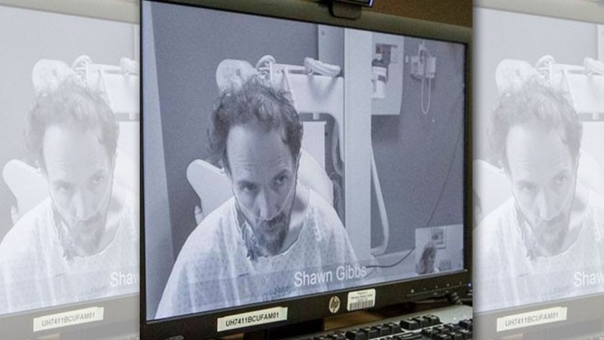 In this photo from Sept. 10, 2014, which was released by the Nebraska Medical Center, Ebola patient Dr. Richard Sacra listens to Bible verses, read to him by his wife Debbie Sacra, unseen, via a video link . Dr. Sacra is being treated at the biocontainment unit at the Nebraska Medical Center in Omaha, Neb. The photo was taken by their son, Max. (AP Photo/Nebraska Medical Center, Max Sacra)