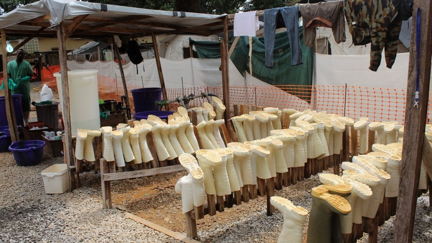 Aug. 20, 2014: In this photo, boots worn by health workers as part of their personal protective equipment are placed on racks to dry after they were washed at a Doctors Without Borders Ebola care center in Conakry, Guinea.