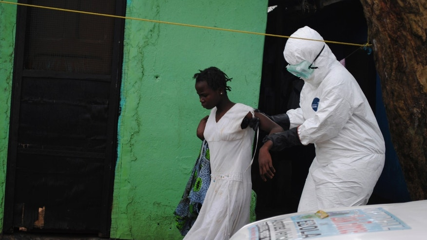 A health worker brings a woman suspected of having contracted the Ebola virus to an ambulance in Monrovia, Liberia, September 15, 2014. REUTERS/James Giahyue