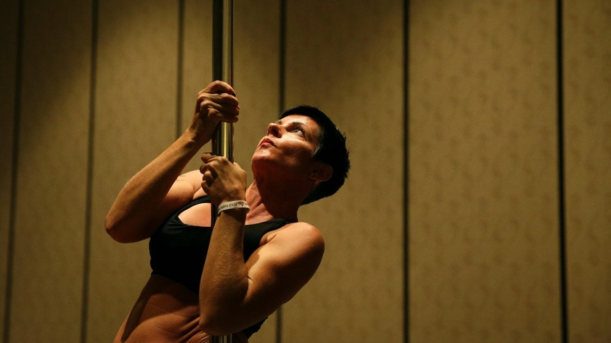 In this Sept. 7, 2014 photo, Heidi Nilsson participates in a workshop at the Pole Expo in Las Vegas. (AP Photo/John Locher)