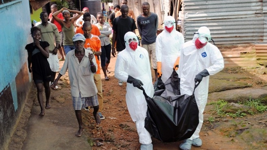 Health workers remove the body of Prince Nyentee, a 29-year-old man whom local residents said died of Ebola virus in Monrovia September 11, 2014. REUTERS/James Giahyue (LIBERIA - Tags: DISASTER HEALTH TPX IMAGES OF THE DAY) - RTR45VJ6