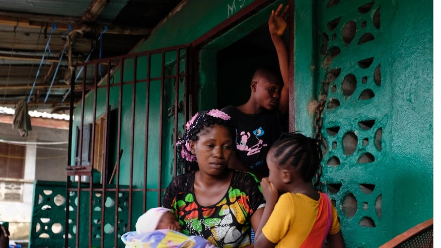 In this picture taken Sunday, Sept. 28, 2014, Finda Saah, 28, holds six-week-old Prosper Junior, as 5 year old Alice and 13-year old son Augustin look on, at their St Paul  Bridge home in Monrovia, Liberia. (AP Photo/Jerome Delay)
