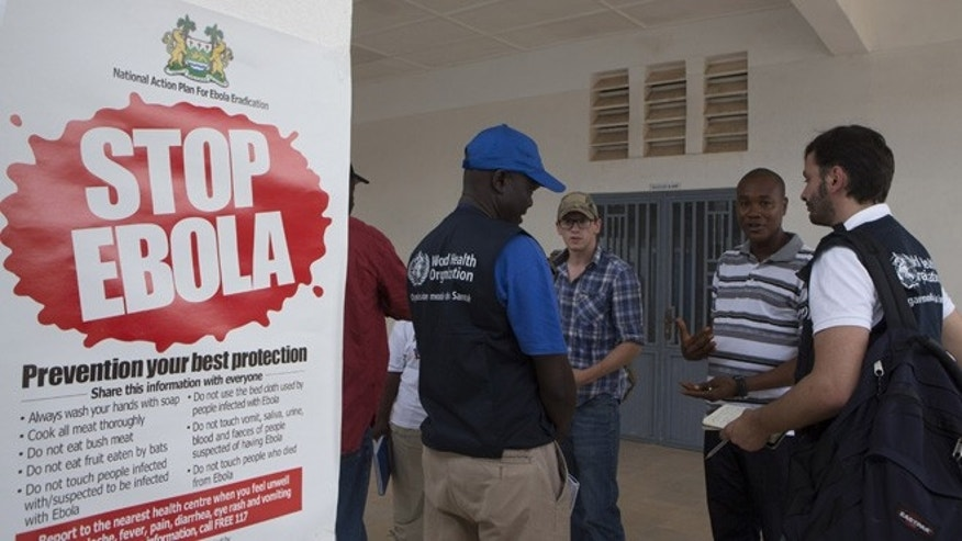 Sept. 27, 2014: WHO members and health directors stand outside the Port Loko District Hospital where the maternity ward has been converted into an isolation holding centre for people with suspected cases of the Ebola virus.