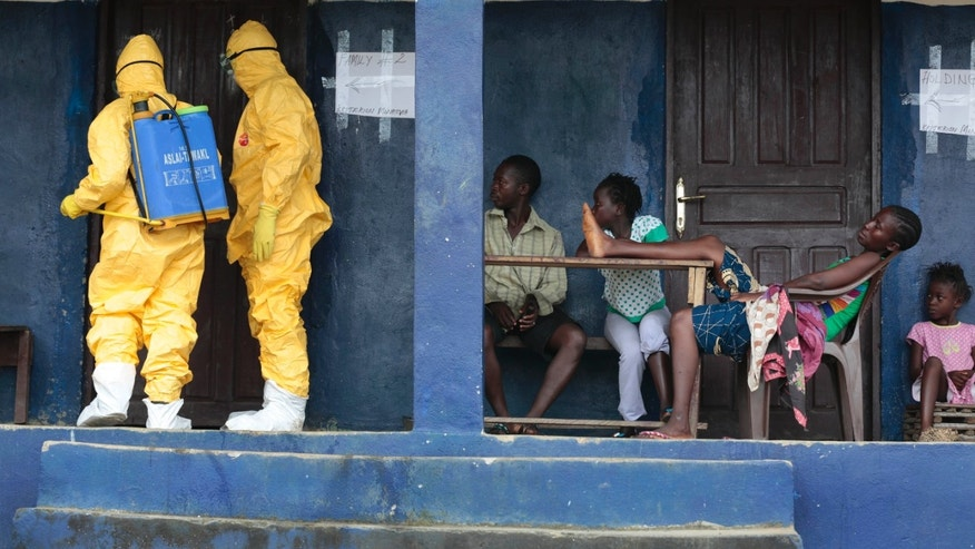 Residents of the village of Freeman Reserve, about 30 miles north of Monrovia, Liberia, watch members of District 13 ambulance service disinfect a room as they pick up six suspected Ebola sufferers that had been quarantined, Tuesday Sept. 30, 2014. AP Photo/Jerome Delay