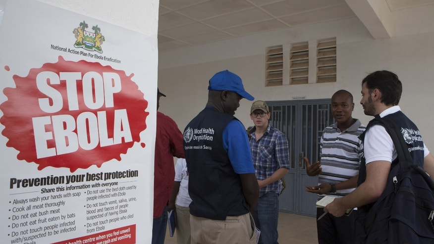 WHO members and health directors stand outside the Port Loko District Hospital September 27, 2014, where the maternity ward has been converted into an isolation holding centre for people with suspected cases of the Ebola virus. REUTERS/Christopher Black/WHO/Handout via Reuters