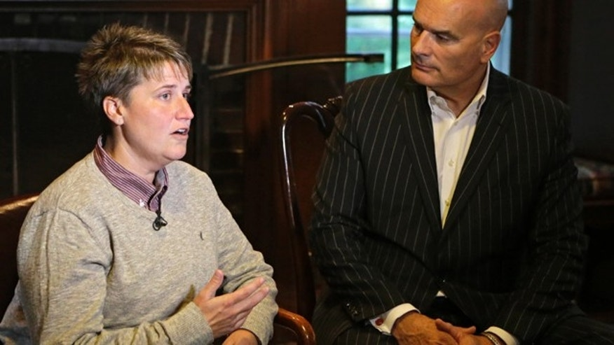 Jennifer Cramblett is interviewed at the home of her attorney, Tim Misny, right, in Waite Hill, Ohio Wednesday, Oct. 1, 2014. Cramblett has sued a Chicago-area sperm bank after she became pregnant with sperm donated by a black man instead of a white man as she'd intended. (AP Photo/Mark Duncan)