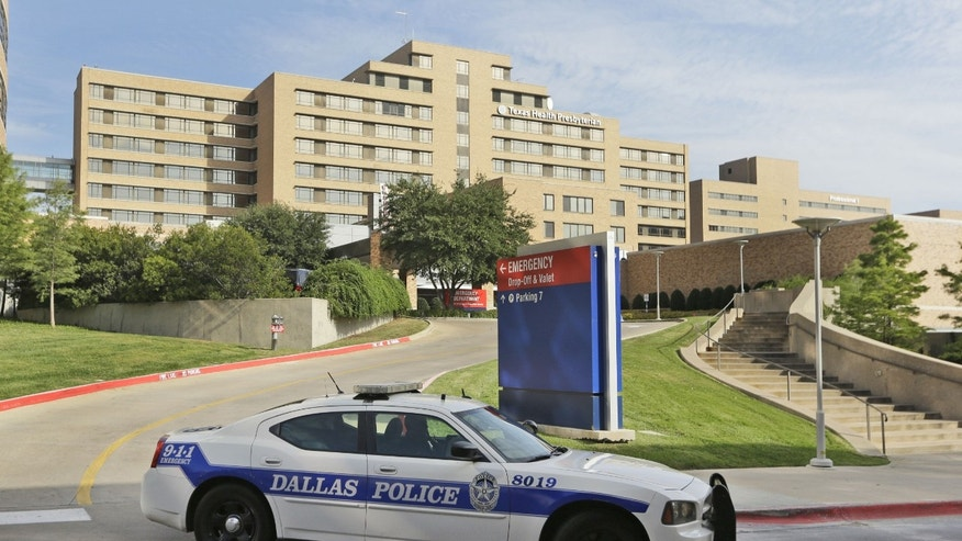 A police car drives past the entrance to the Texas Health Presbyterian Hospital in Dallas, Tuesday, Sept. 30, 2014. (AP Photo/LM Otero)