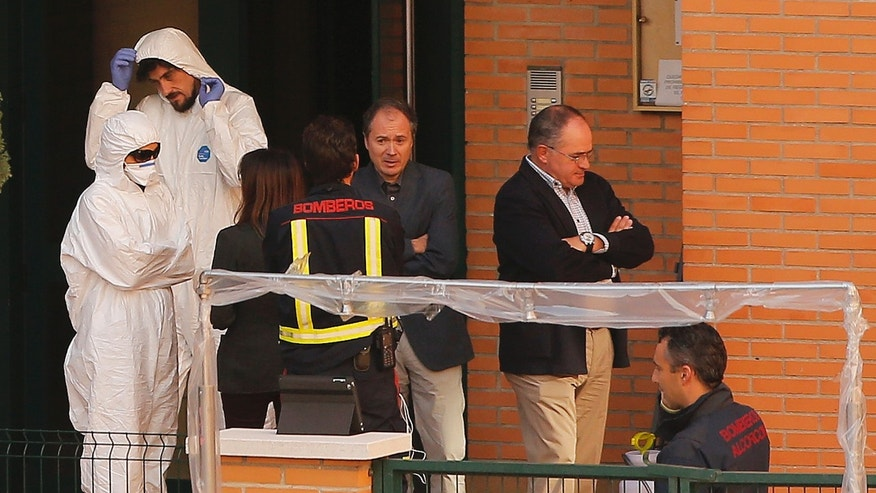 Firemen stand as worker wearing rompers and gloves come out ofthe building entrance of the apartment building of the Spanish nurse infected with Ebola in Madrid, Spain, Wednesday, Oct. 8, 2014. (AP Photo/Andres Kudacki)