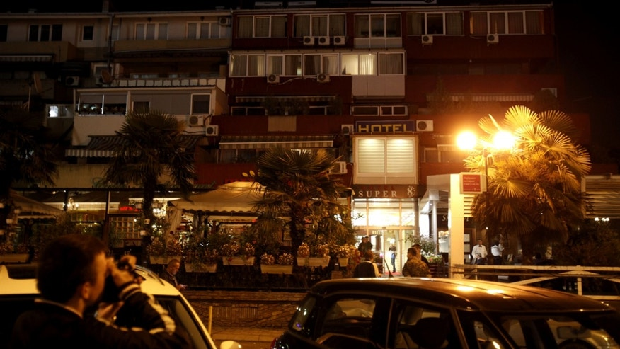 Oct. 9, 2014: People stand outside the hotel where a 58-year-old man was taken to hospital and died of severe internal bleeding shortly, in Skopje.