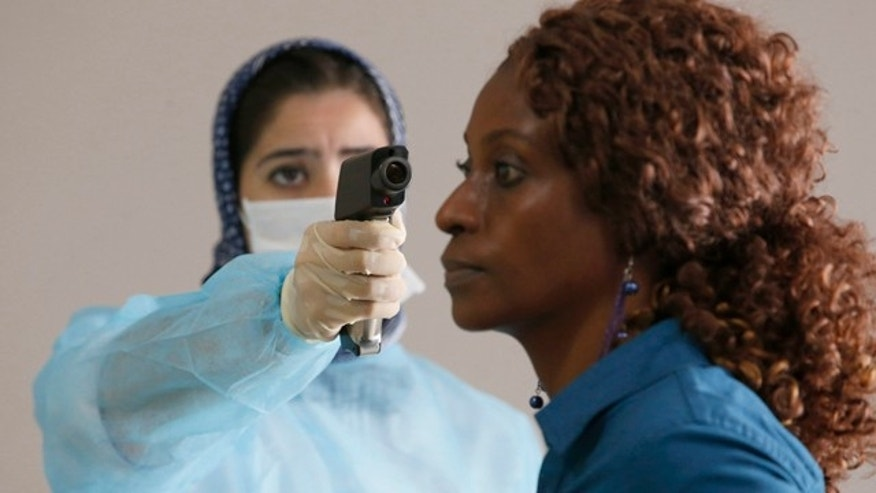 October 9, 2014: A Moroccan health worker uses a thermometer to screen a passenger at the arrivals hall of the Mohammed V airport in Casablanca. (AP Photo/The Canadian Press, Abdeljalil Bounhar)