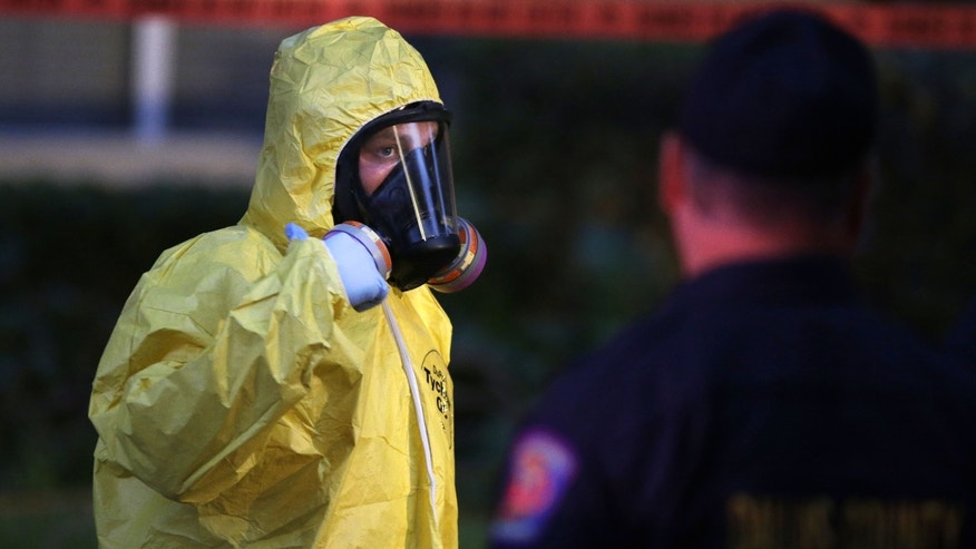 A hazmat worker cleaning outside an apartment building of a hospital worker, Sunday, Oct. 12, 2014, in Dallas.