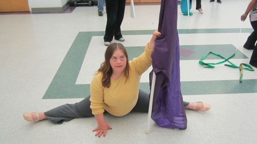 A member of the color guard practices her routine.