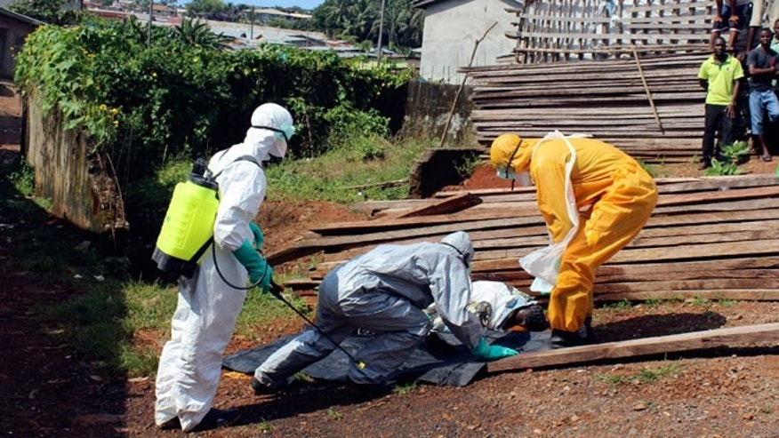 Health workers remove the body a woman who died from the Ebola virus in the Aberdeen district of Freetown, Sierra Leone, October 14, 2014.
