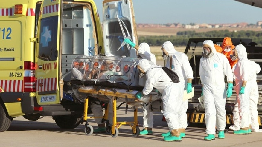 In this photo provided by the Spanish Defense Ministry, aid workers and doctors transfer Miguel Pajares, a Spanish priest who was infected with the Ebola virus while working in Liberia, from a plane to an ambulance as he leaves a military airbase, near Madrid, Spain. Teresa Romero, 44, a nursing assistant, reportedly became infected with Ebola while caring for Pajares.