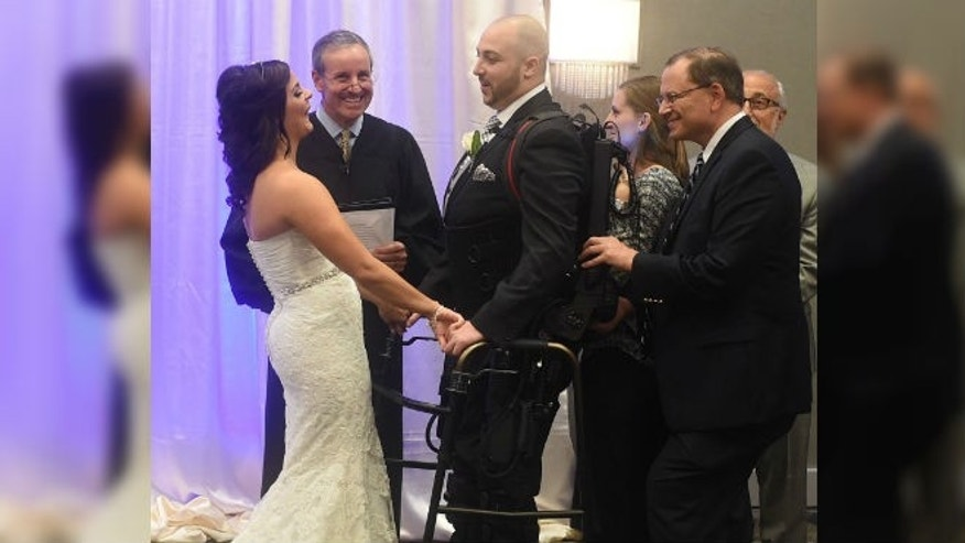 Jordan Basile, left, and Matt Ficarra, center, exchange wedding vows Saturday, Oct. 18, 2014, at the Doubletree hotel in Syracuse, N.Y. (AP Photo/The Syracuse Newspapers, Dennis Nett)