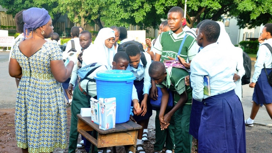Students of Goverment Secondary School Garki wash their hands, as school resumes in Abuja September 22, 2014. REUTERS/Stringer