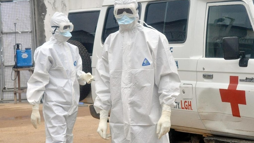 Health workers wearing protective gear wait to carry the body of a person suspected to have died from Ebola, in Monrovia, Liberia, Monday Oct. 13, 2014. (AP Photo/Abbas Dulleh)