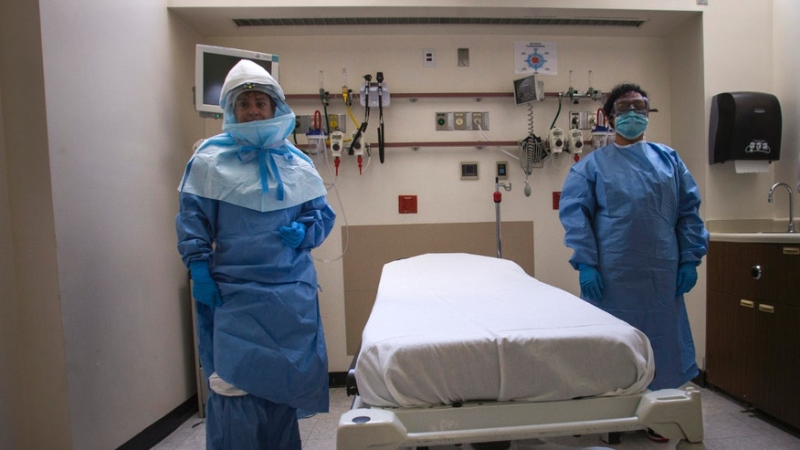 Health care workers display protective gear, which hospital staff would wear to protect them from an Ebola virus infection, inside an isolation room as part of a media tour of the emergency department of Bellevue Hospital in Manhattan, New York October 8, 2014.   REUTERS/Adrees Latif