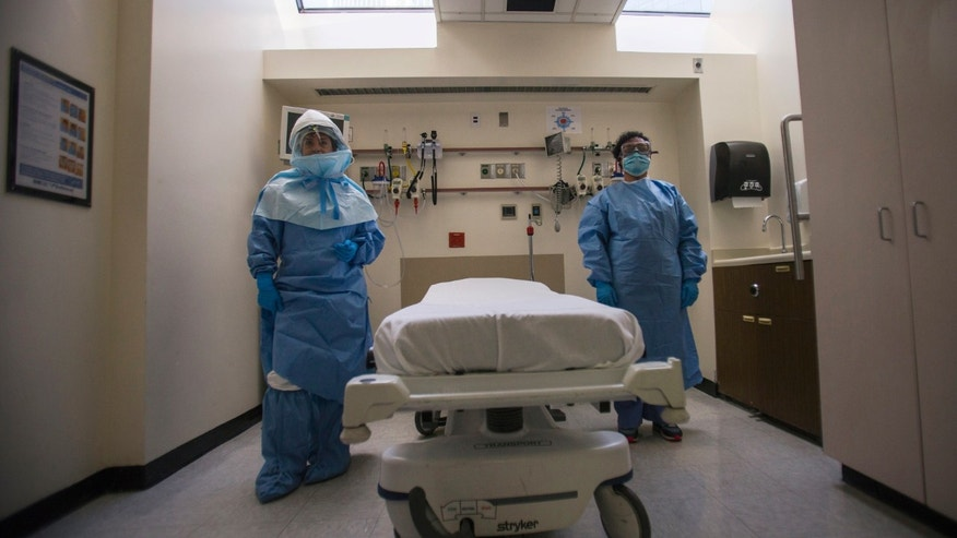 Oct. 8, 2014: Health care workers display protective gear, which hospital staff would wear to protect them from an Ebola virus infection, inside an isolation room as part of a media tour in the emergency department of Bellevue Hospital in Manhattan, New York.