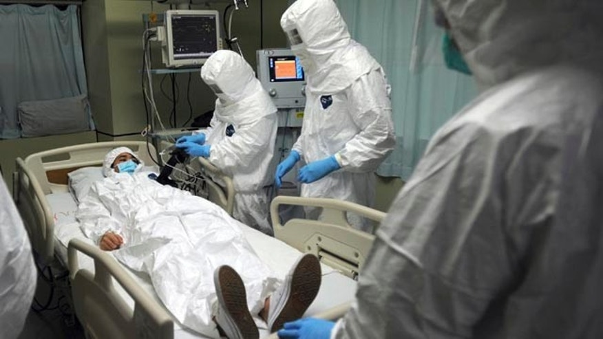 October 23, 2014: Medical workers wearing protective suits treat a mock patient during a training exercise on dealing with a suspected Ebola case at a hospital in Guangzhou in south China's Guangdong province. (AP Photo)