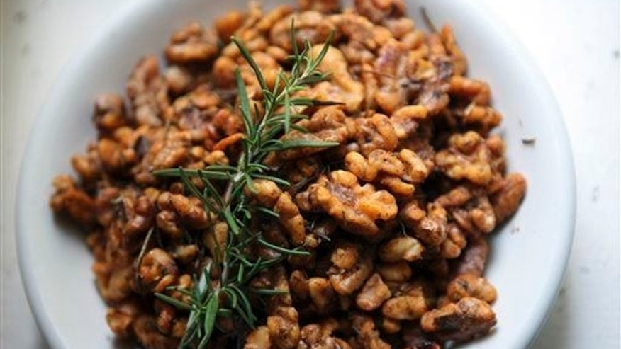 In this July 8, 2014 photo, a sprig of rosemary garnishes walnuts.