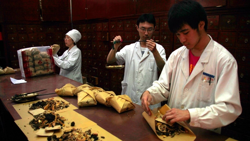 Workers prepare traditional Chinese herbal medicines at Beijing's Capital Medical University Traditional Chinese Medicine Hospital May 25, 2011.    REUTERS/David Gray