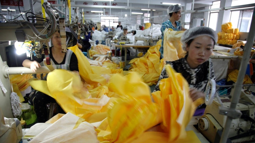 In this photo taken Thursday, Oct. 30, 2014, Chinese workers manufacture protection suits that meet the standards for use by healthcare workers treating Ebola patients at a factory of U.S. based Lakeland Industries in Anqiu city in eastern China's Shandong Province. (AP Photo/Wayne Zhang)