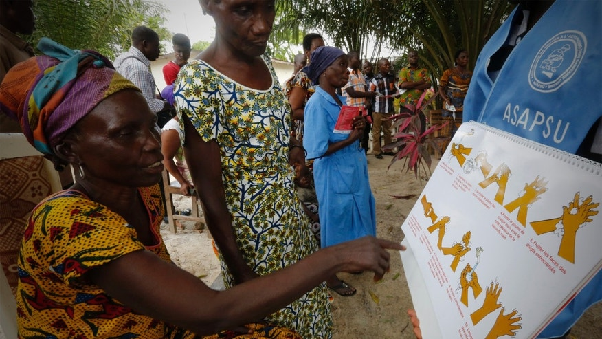 Women look at a poster on Ebola prevention at Toulepleu, at the border of Liberia in western Ivory Coast, November 4, 2014.  Picture taken November 4, 2014. REUTERS/Thierry Gouegnon