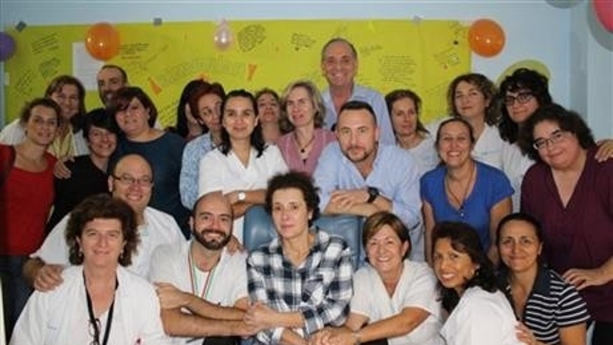This Nov. 1, 2014 photo provided by the Madrid's Carlos III hospital shows Teresa Romero, center, posing for a photo with medical workers and friends after leaving the isolation unit in the Carlos III hospital in Madrid, Spain.