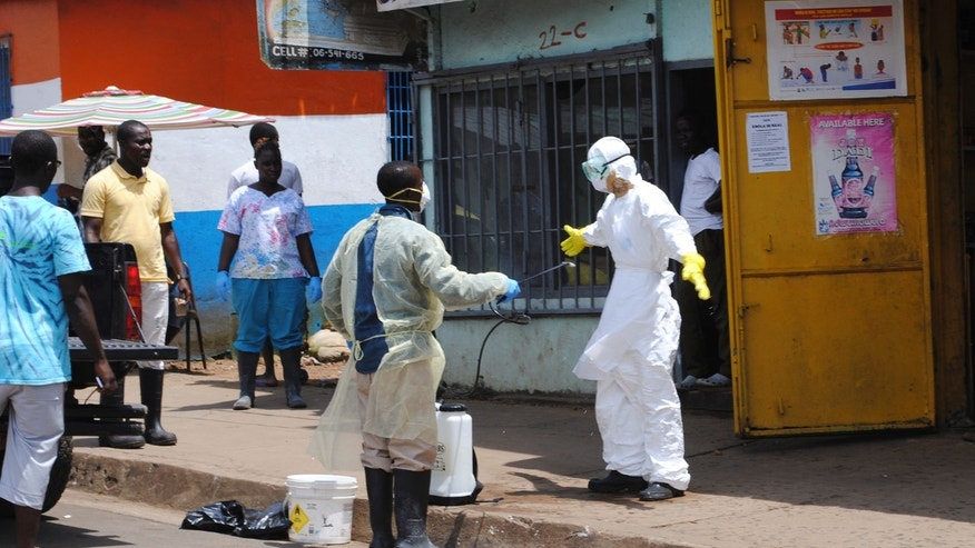 A member of a burial team sprays a colleague with chlorine disinfectant in Monrovia October 20, 2014. The worst epidemic on record of the deadly virus Ebola has now killed more than 4,500 people in Liberia, Sierra Leone and Guinea. REUTERS/James Giahyue