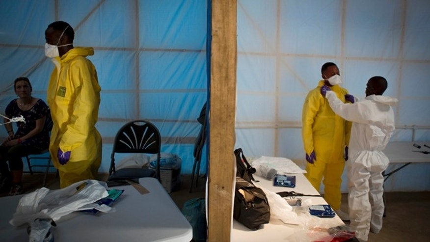 This undated handout photo issued by Save the Children UK on Wednesday, Nov. 5, 2014, shows prospective health care workers in the Kerry Town Ebola Treatment Centre being tested on their personal protection equipment procedure in Sierra Leone.  The center in Kerry Town includes an 80-bed facility to be managed by Save The Children and a 12-bed unit, which will expand to 20 beds over the coming months, for health care workers and international staff who become infected by Ebola. (AP Photo, Louis Leeson/Save the Children UK)