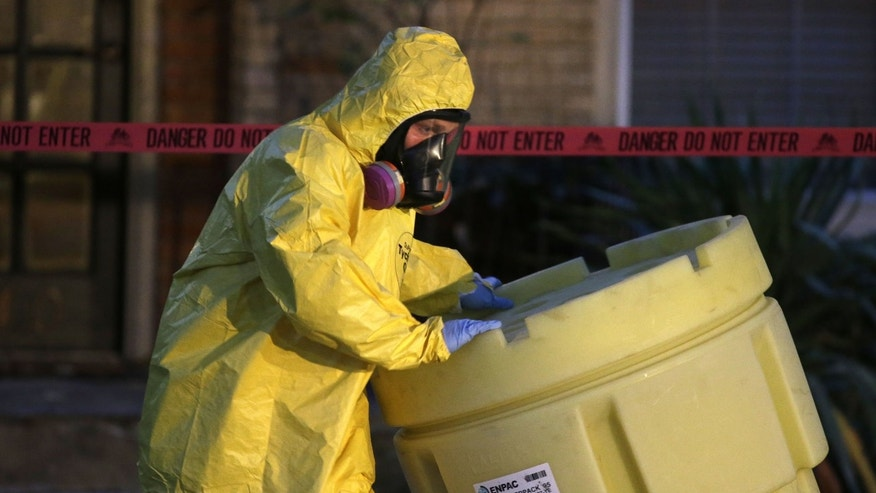Oct. 12, 2014: A hazmat worker moves a barrel while finishing up cleaning outside an apartment building of a hospital worker in Dallas.