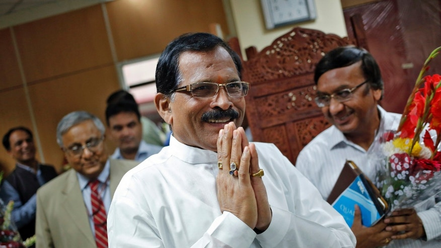 Shripad Naik, India';s new minister in charge of the department of Ayurveda, Yoga and Naturopathy, Unani, Siddha and Homeopathy (AYUSH), greets the media as he arrives to take charge of his office in New Delhi November 11, 2014. REUTERS/Anindito Mukherjee