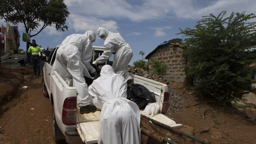 A burial team wearing protective clothing, remove a body of a person suspected of having died of the Ebola virus, in Freetown September 28, 2014. REUTERS/Christopher Black/WHO/Handout via Reuters