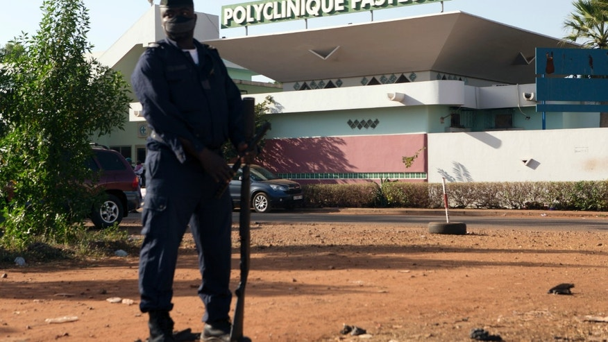 A police officer stands guard outside the quarantined Pasteur Clinic in Bamako November 12, 2014. REUTERS/Joe Penney