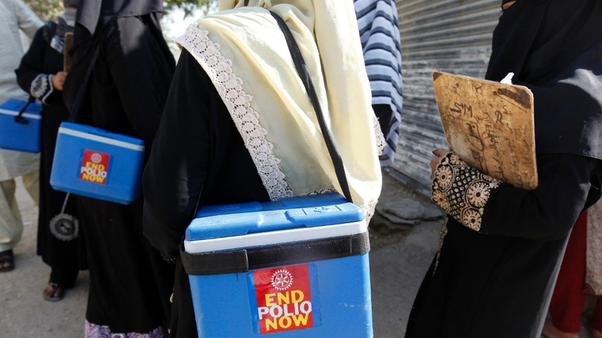 Polio vaccinators carry boxes of polio vaccine drops as they head to the areas they have been appointed to administer the vaccine, in Karachi October 21, 2014. REUTERS/Akhtar Soomro