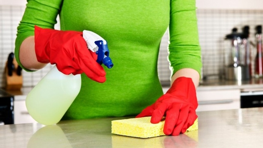 Girl cleaning kitchen  with sponge and rubber gloves