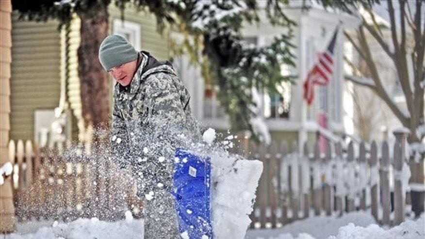 Spc. Cory Amato, from Fort Drumm, shovels snow from the sidewalk outside his house on Franklin Street Wednesday, Nov. 19, 2014, in Watertown, N.Y.