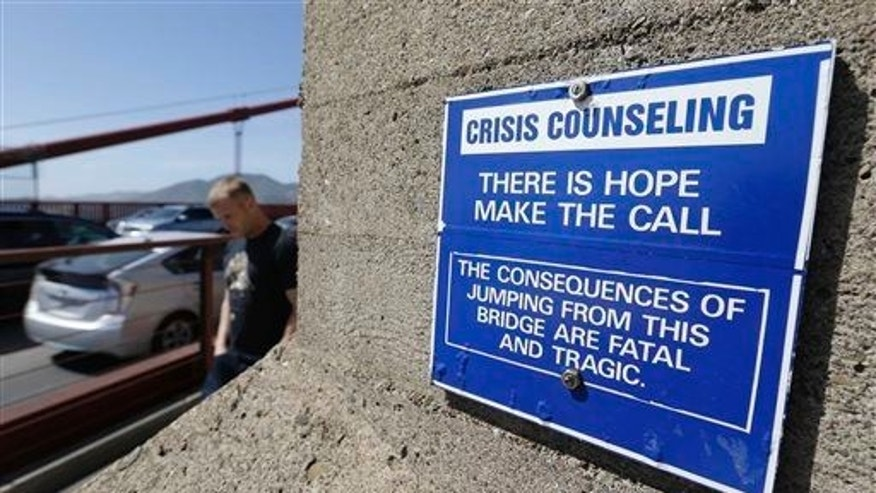 A sign is posted above a crisis counseling call box on the Golden Gate Bridge in San Francisco.