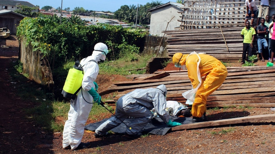 Health workers remove the body a woman who died from the Ebola virus in the Aberdeen district of Freetown, Sierra Leone, October 14, 2014. REUTERS/Josephus Olu-Mammah