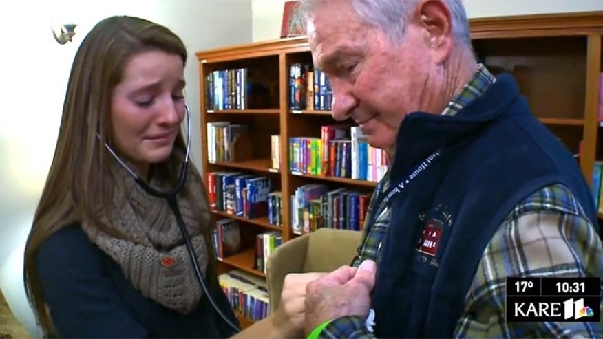 Casey Heilser, listens to the chest of Tom Meeks who received her brother Matt's heart in a life-saving transplant.