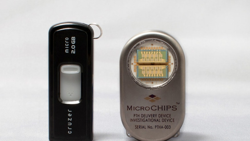A photo of the drug delivery device, right, next to an everyday computer memory stick. (AP Photo/MicroCHIPS, Inc., Massachusetts)
